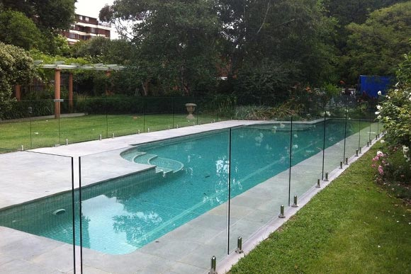 Outdoor pool with frameless fencing installed by lawn