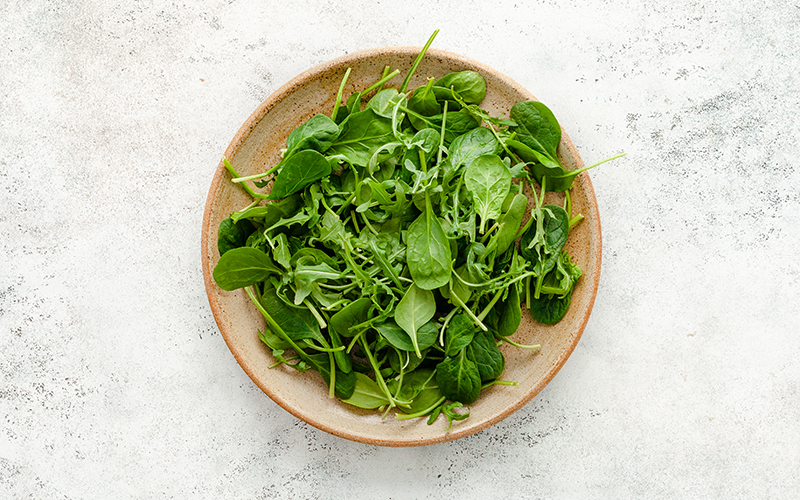 The first step to a delicious vegan salad is to pile on those leafy greens, including kale, lettuce, spinach, arugula, and fresh herbs!