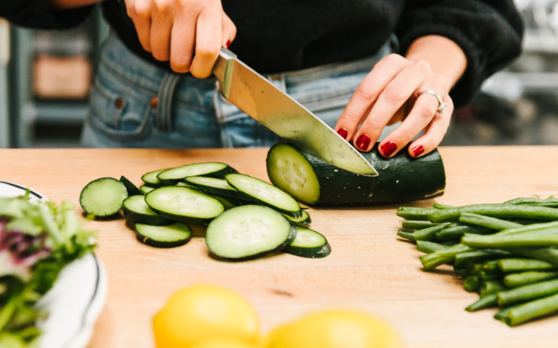 Prep the veggies for your nicoise salad through slicing both your cucumbers and heirloom cherry tomatoes.