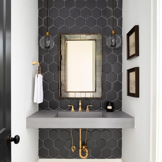 Chic black and gold powder room features clear glass pendants hung on either side of a brass tiled mirror hung from an accent wall clad in black hexagon backsplash tiles over a gray concrete sink vanity finished with a brass faucet.