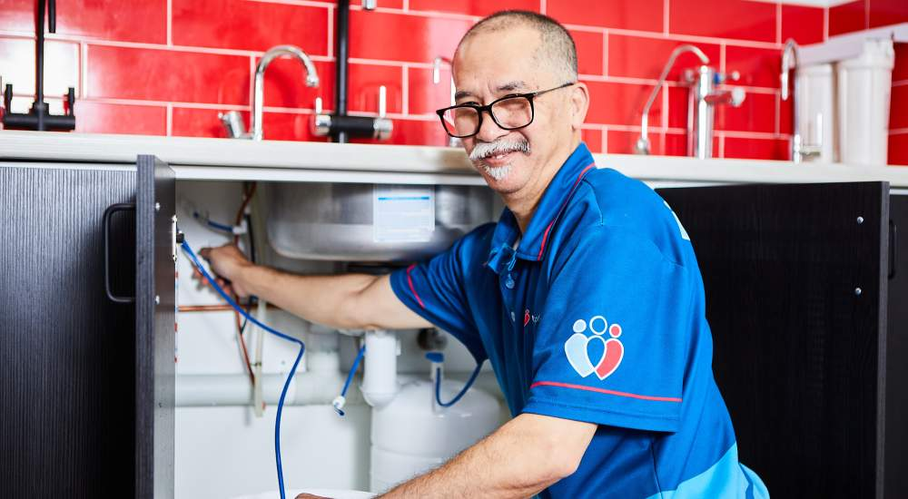 technician performing servicing of a filtered water tap