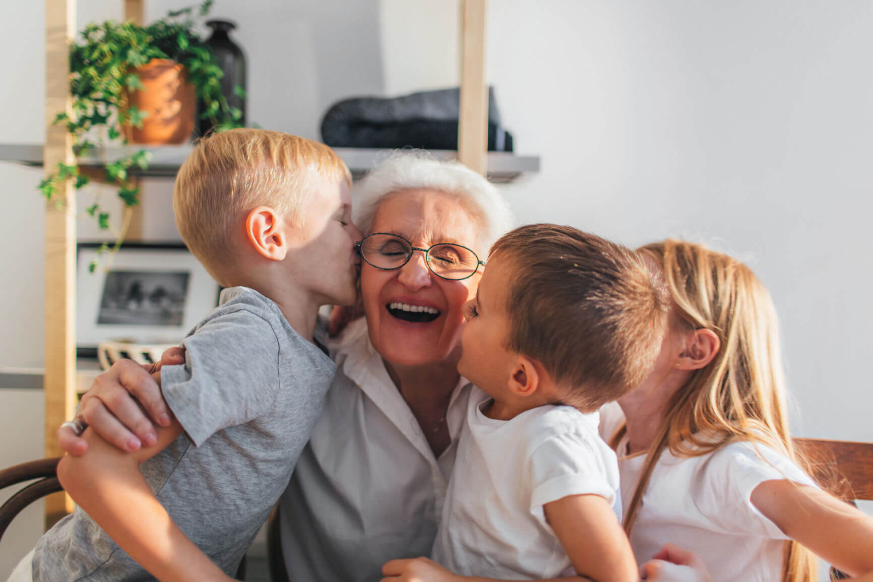 A woman smiles with her grandchildren.