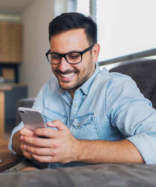 Young man smiling at his phone