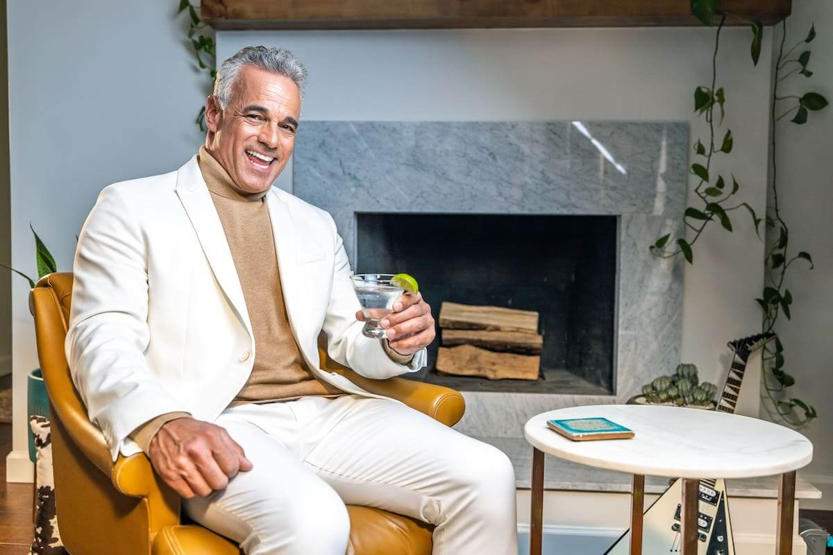 A gentleman smiling as he sits next to a fireplace with a drink.