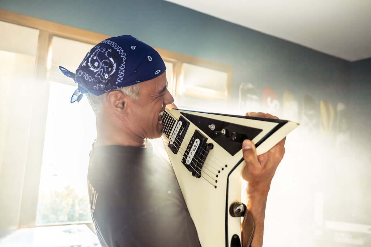 Man with bandana on playing an electric guitar with his teeth