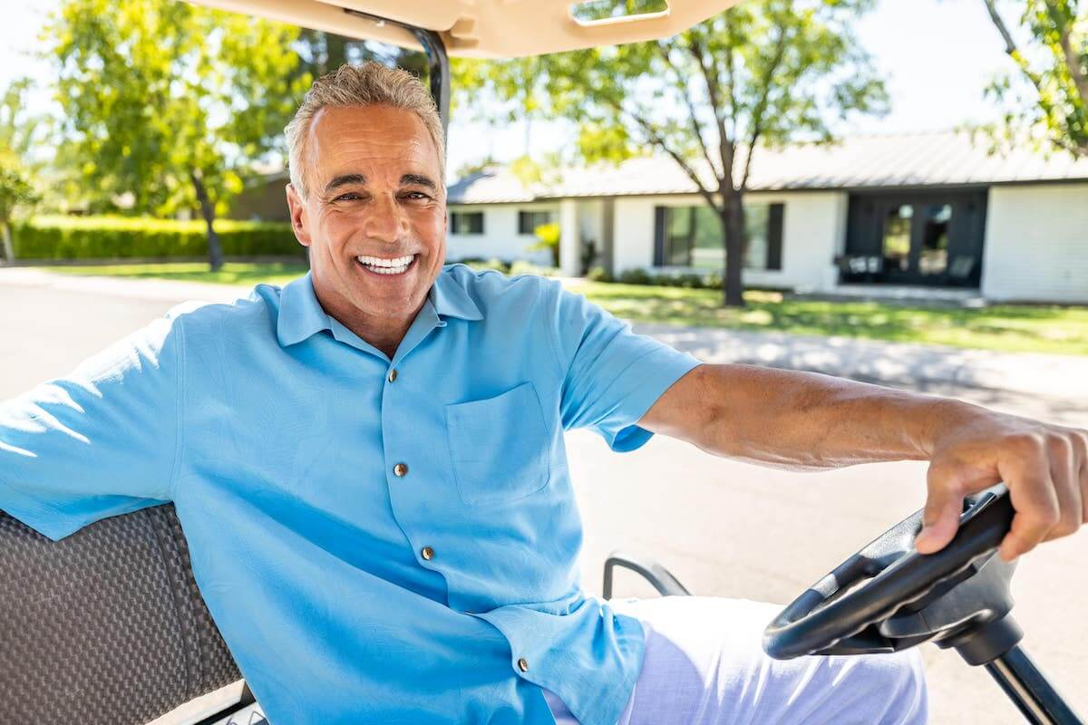 Portrait of a middle aged man smiling as he drives a golf cart