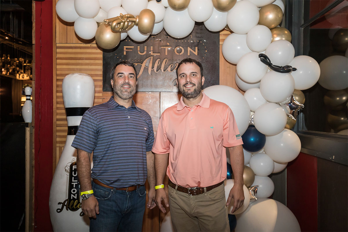 Jay and Chad Himmel in front of a Fulton Alley bowling sign with balloons around them