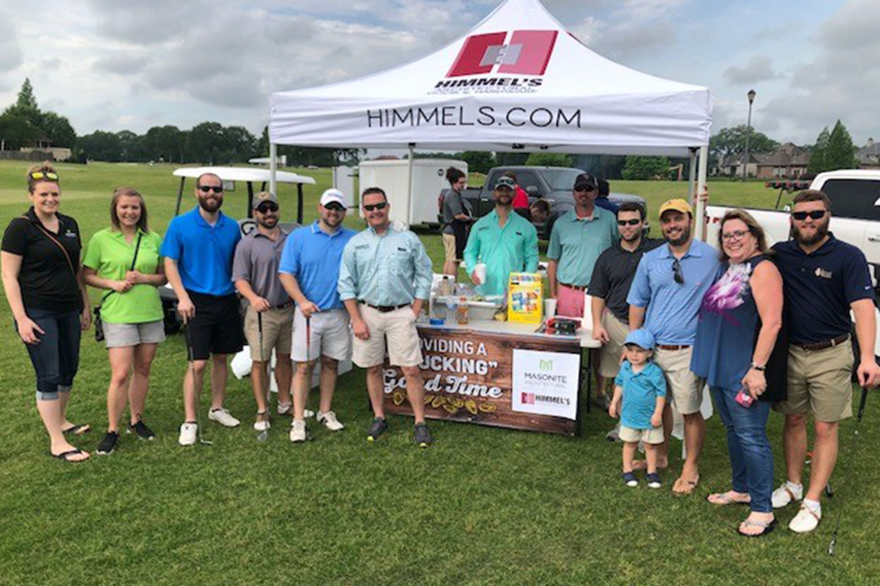Group of Himmel employees by a tent at their Annual Golf Tournament