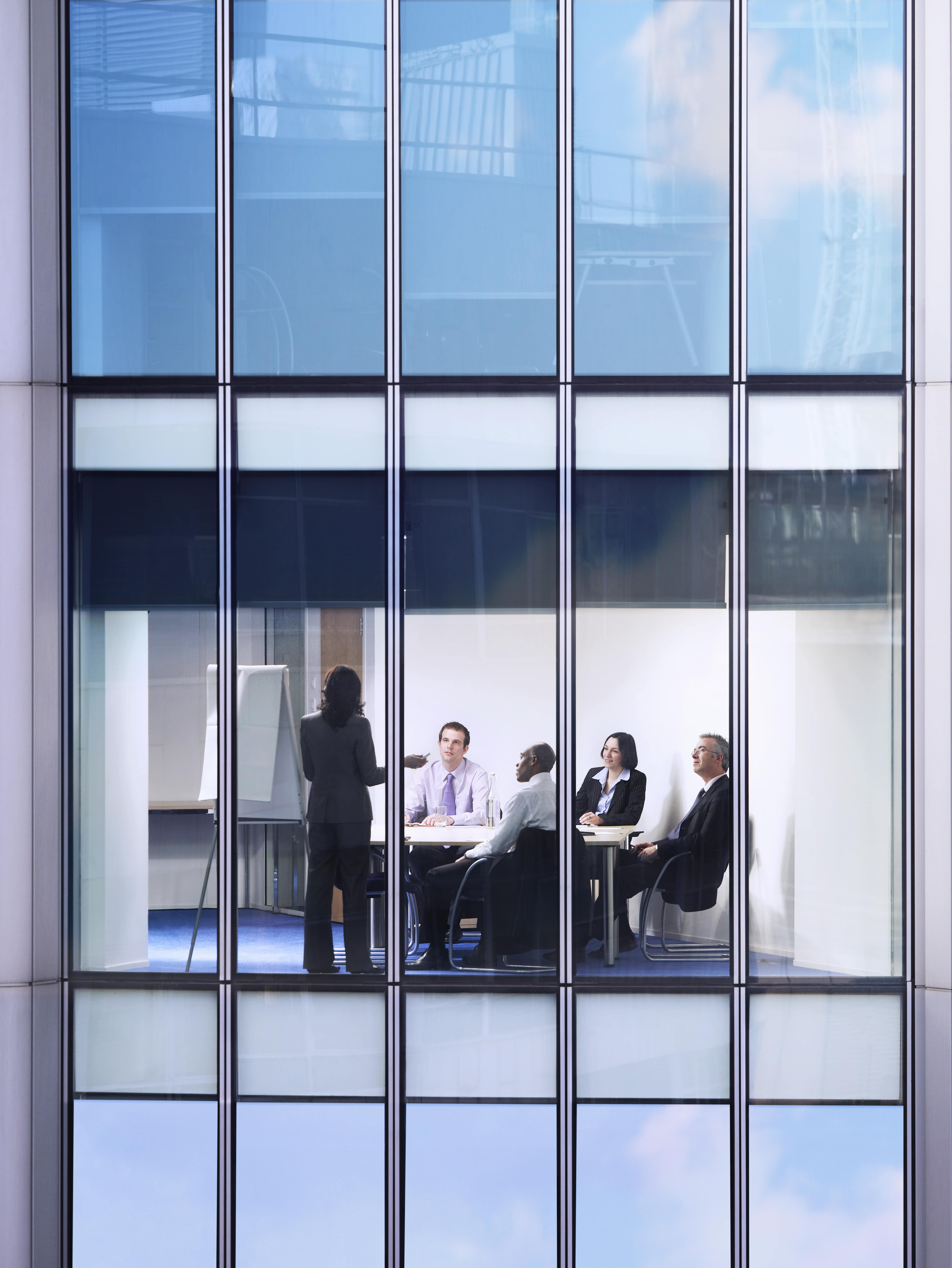 Image of a business meeting through a building window