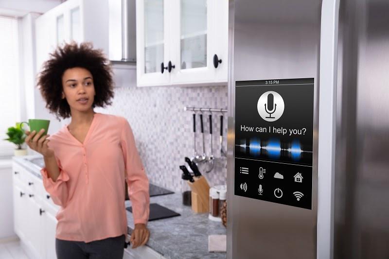 Mujer hablando con un asistente virtual integrado en la nevera de la cocina.