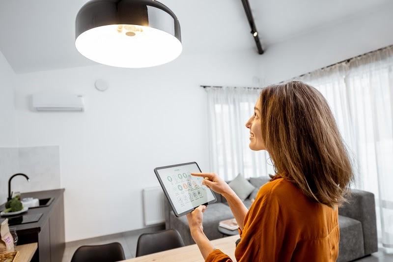 Mujer que usa una tableta para configurar los creadores de humor de iluminación inteligente en casa