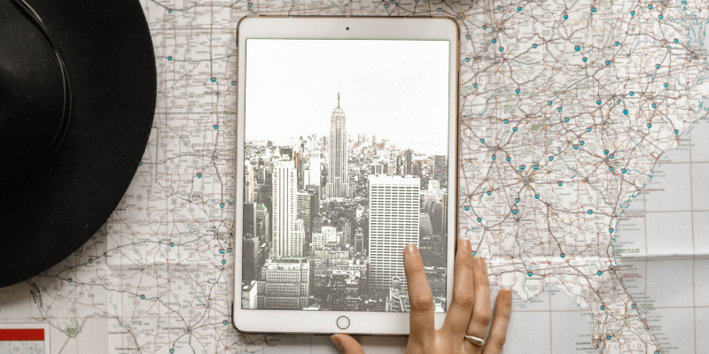 Map with a tablet on it with a bird eye's image of a city (assumably the city on the map)