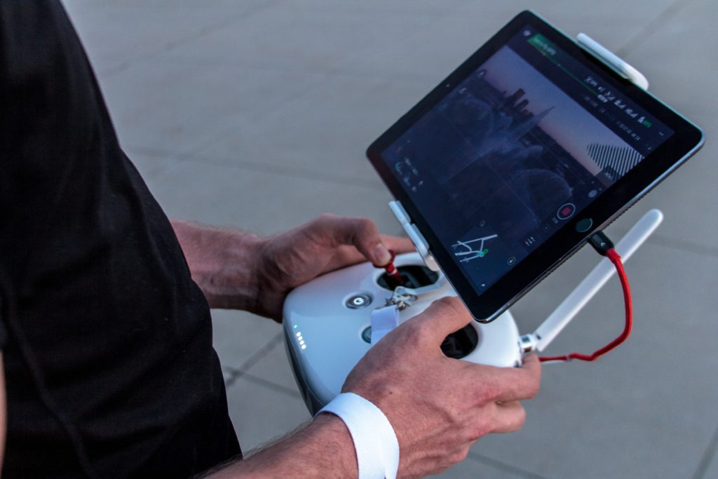 Person piloting a drone from a handheld controller