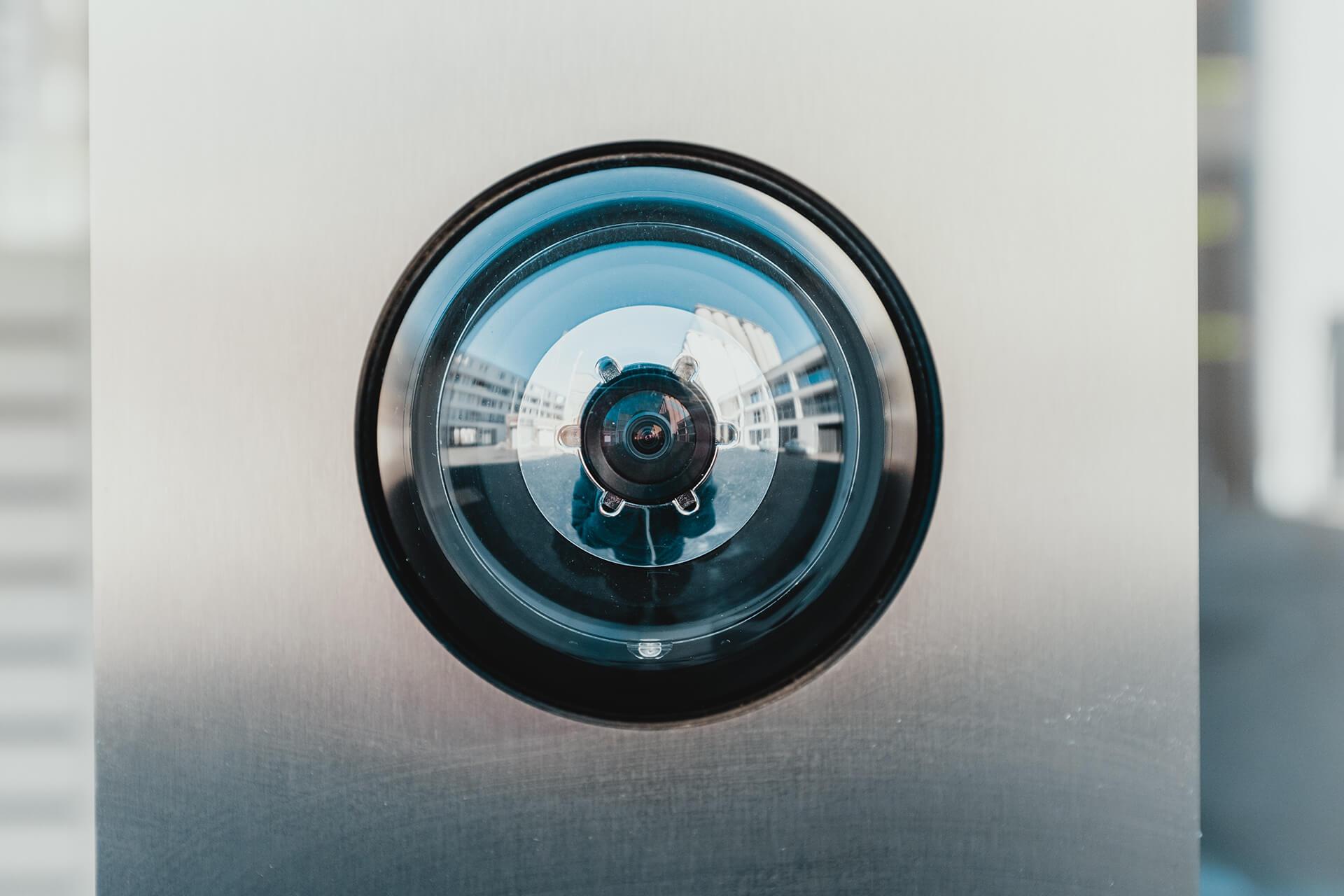 A circular security camera mounted on a wall