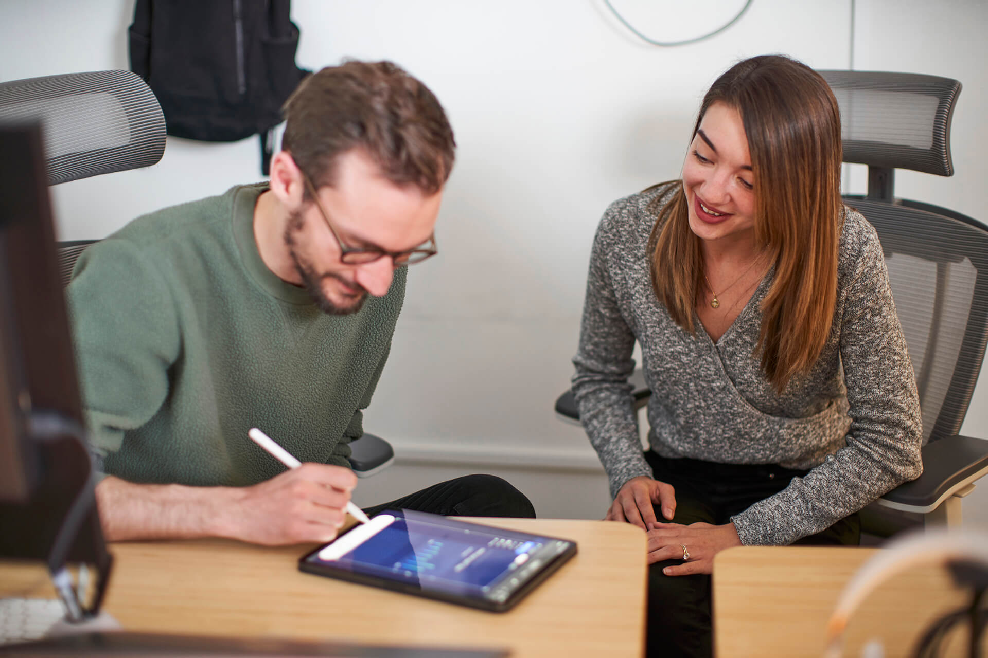 Hologram Senior Product Designer Sean Nelson and Sales Manager Allison Blade collaborate over an iPad in the Hologram office.