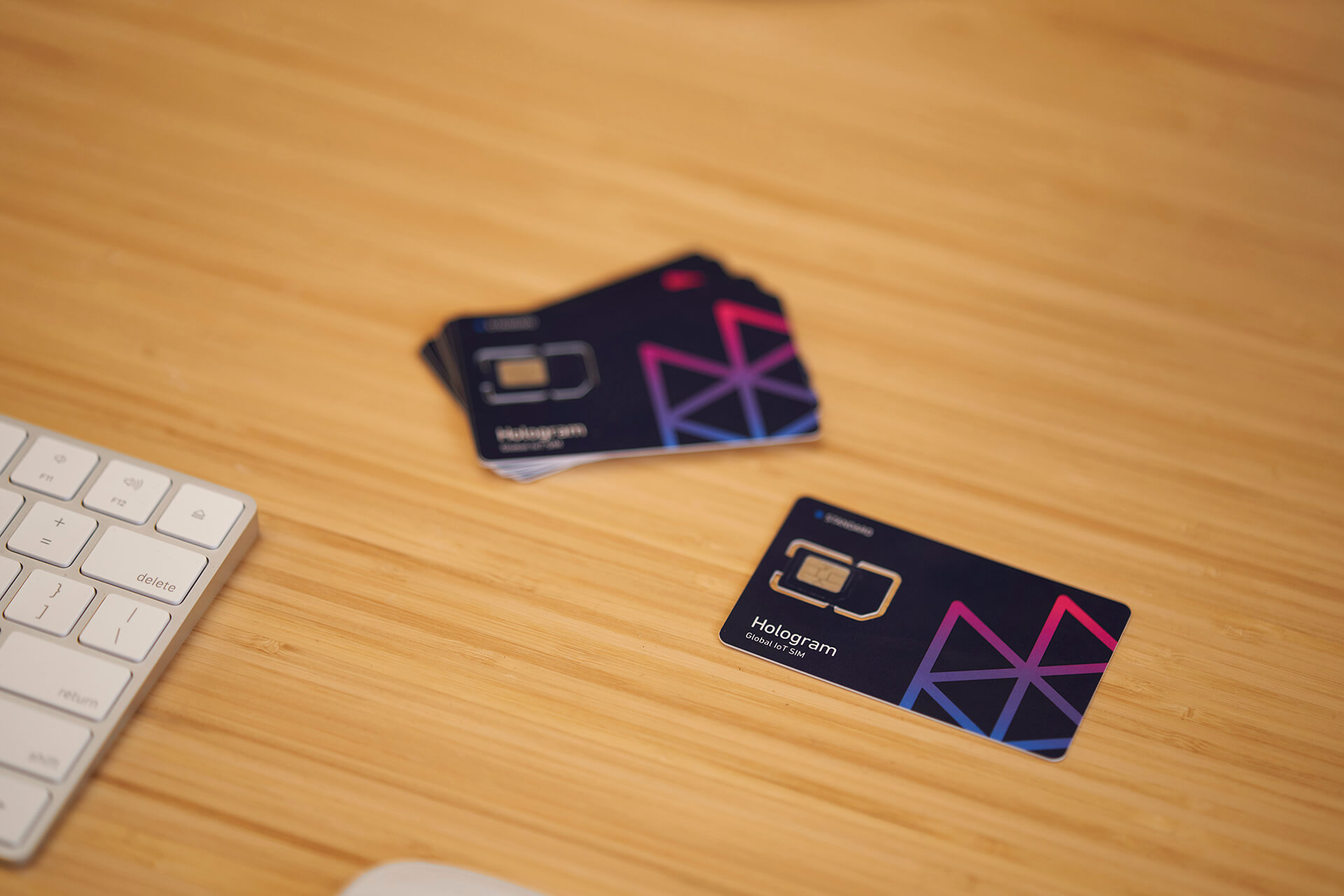 Hologram SIM cards on a wooden table next to a keyboard.