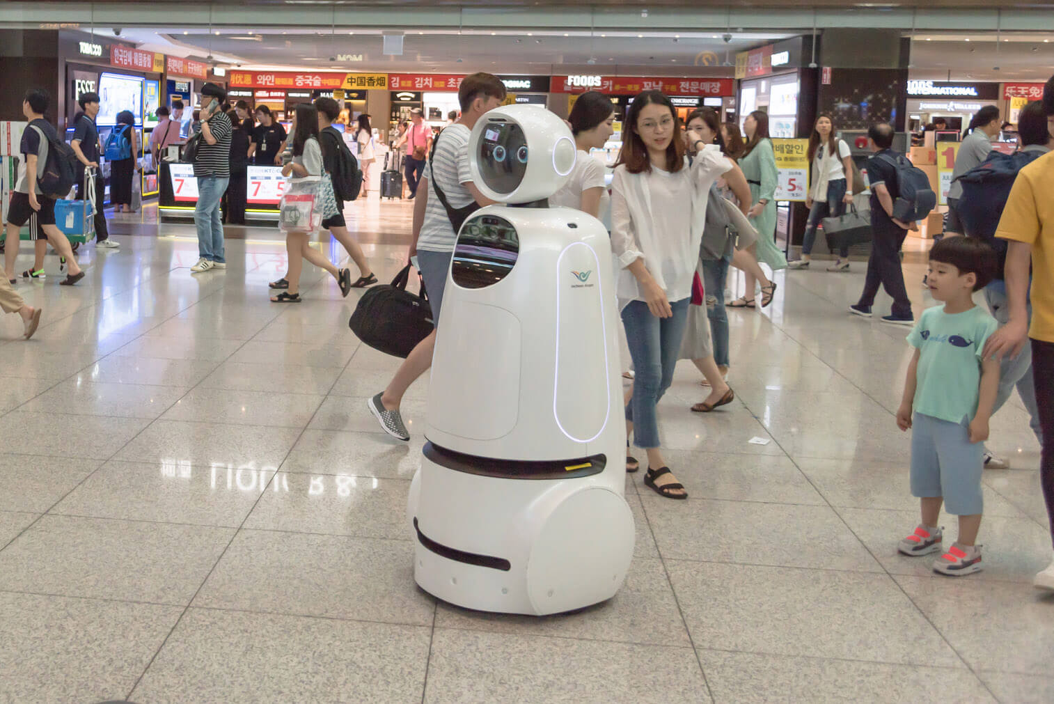 A retail robot roams in a crowded mall