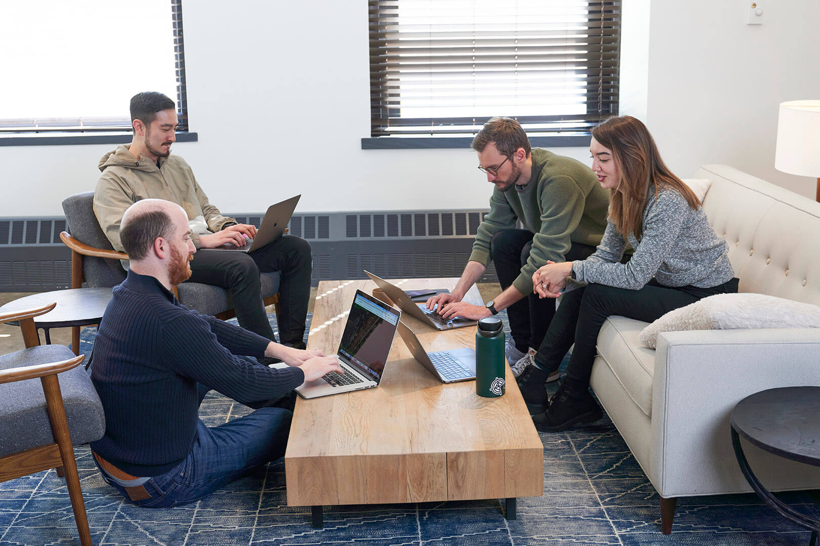 Hologrammers sit around a coffee table in the office and work together