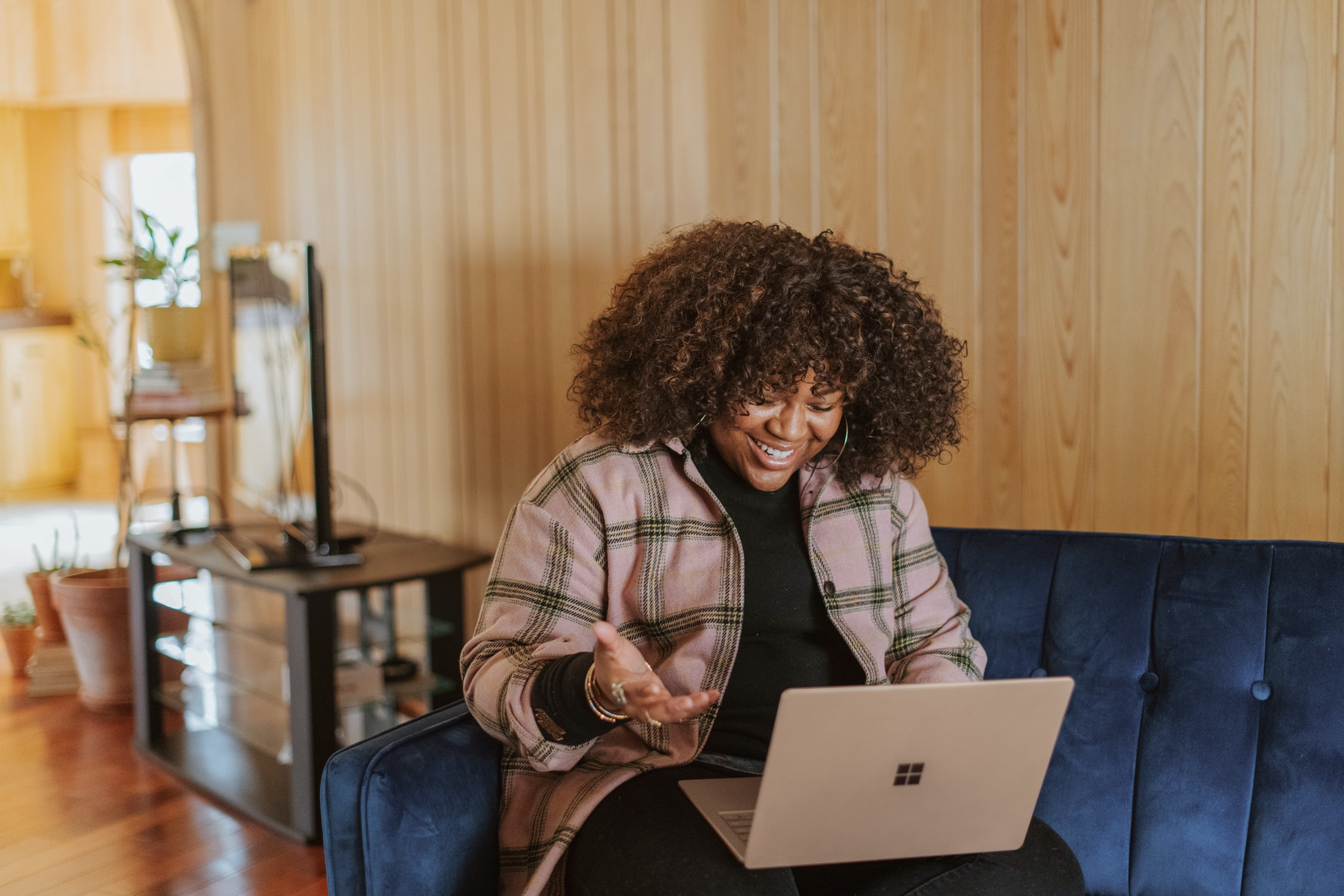 Woman working remote sitting on her couch on a call