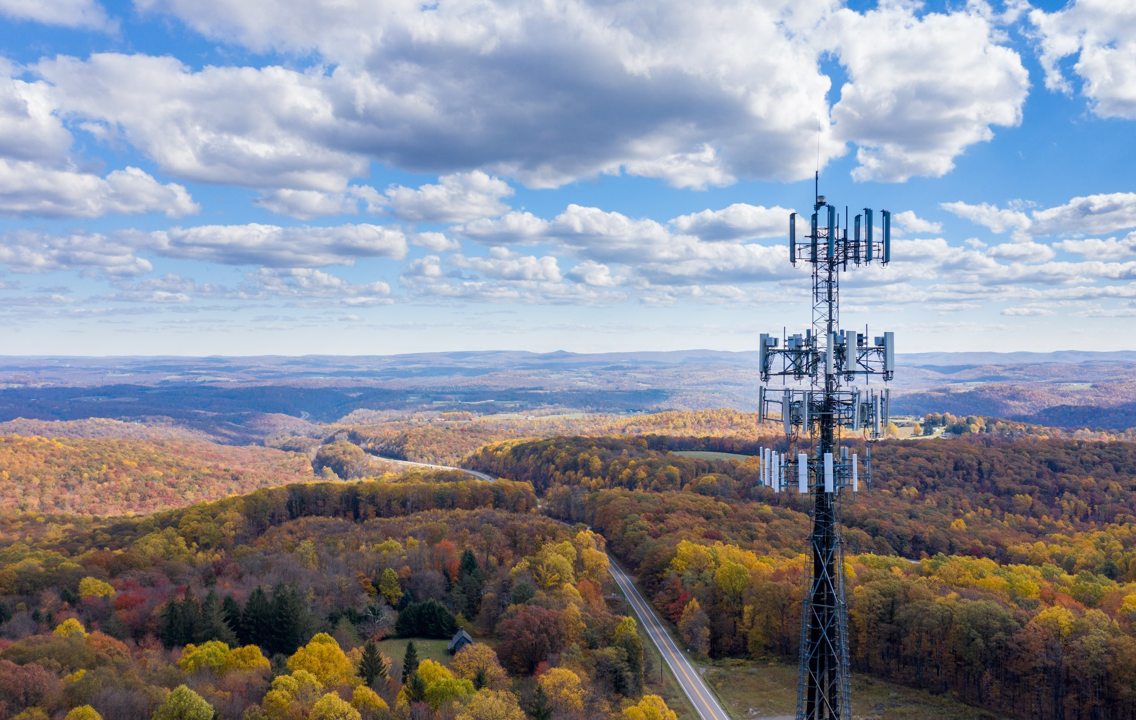 Cell tower overlooking a forest in the fall