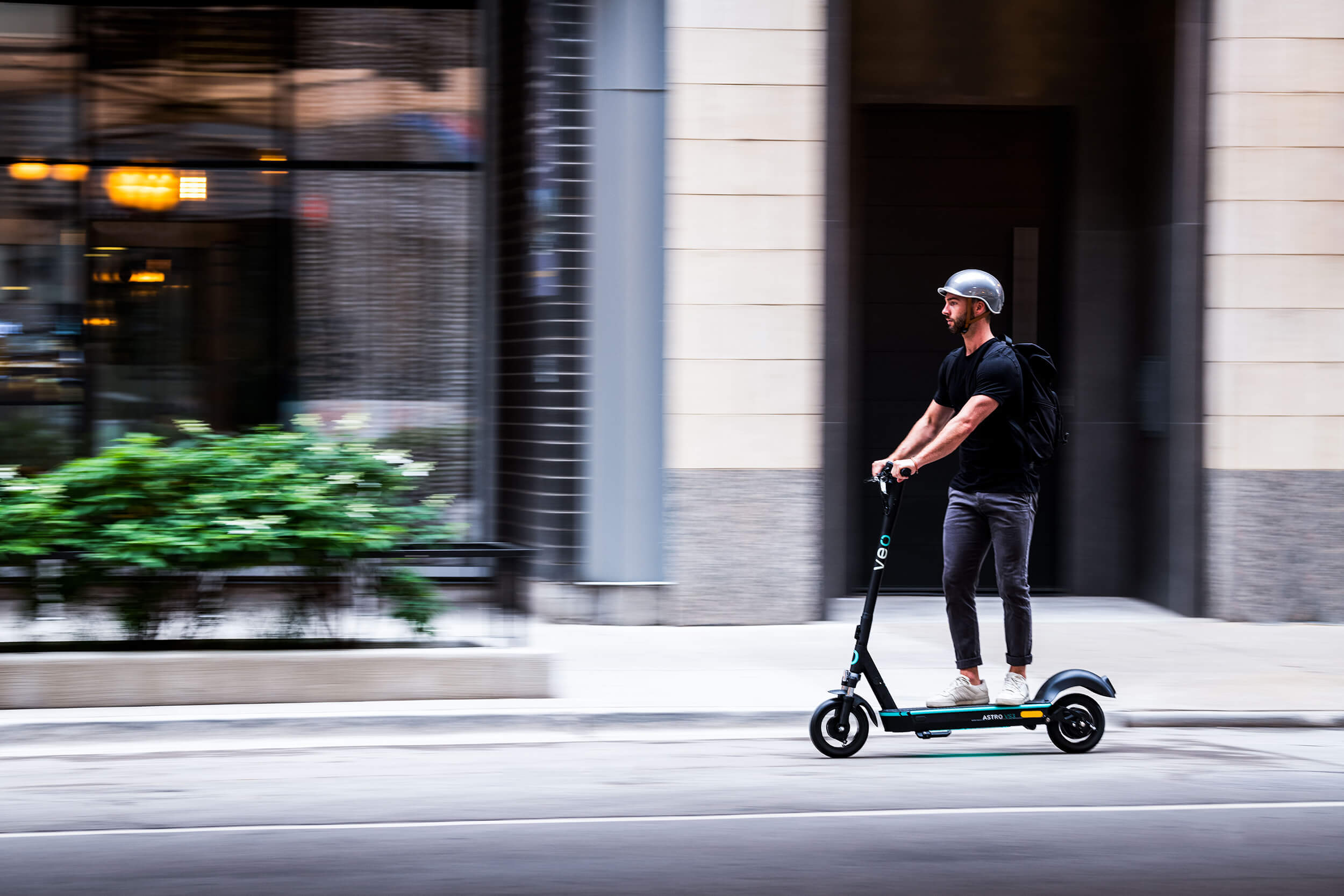 Man riding Veo scooter on a city street