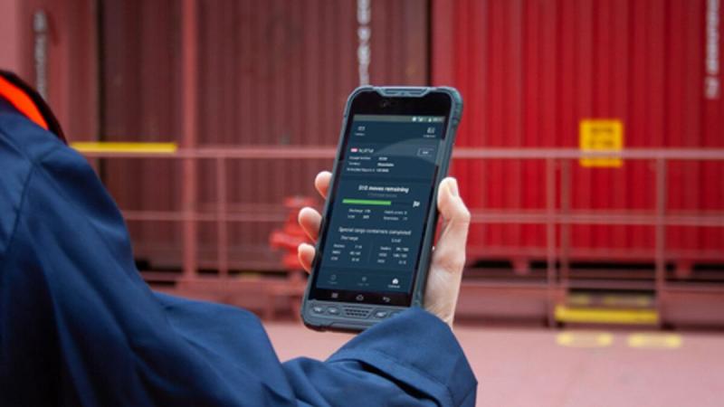 man looking at cell phone monitoring industrial shipping