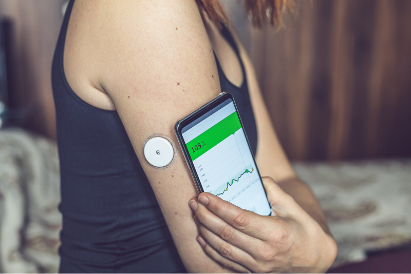 woman using a cell phone to track a health monitoring device on her arm