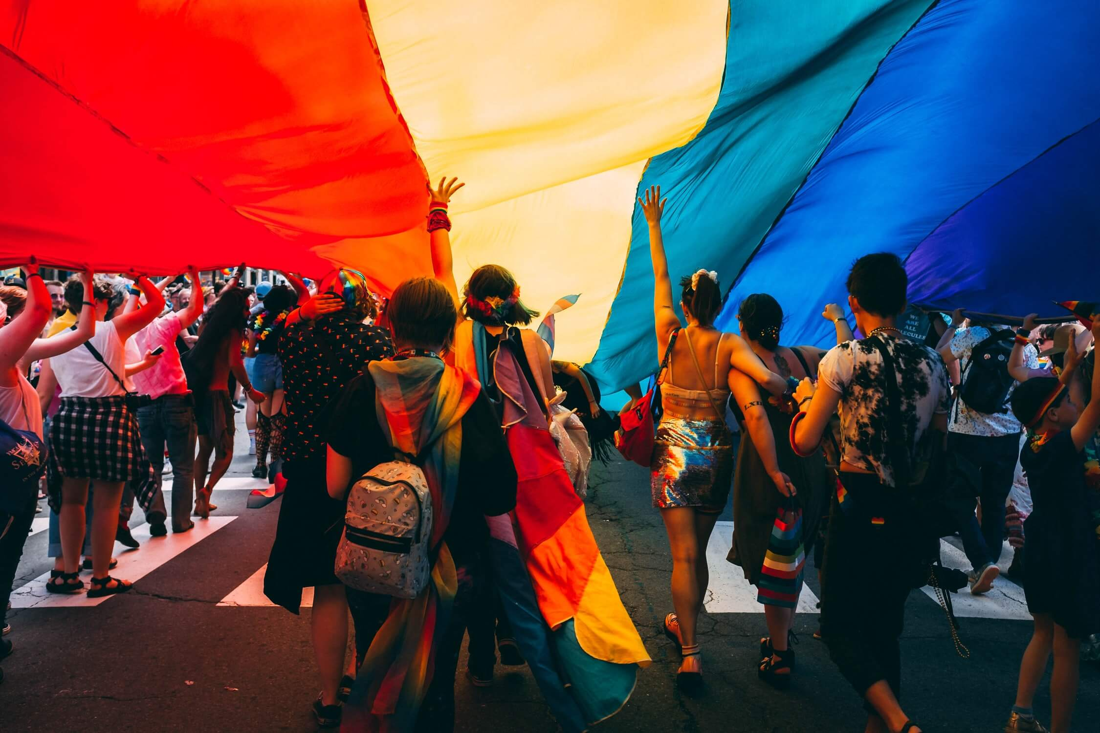 People walking under a gigantic flag during the annual Pride parade