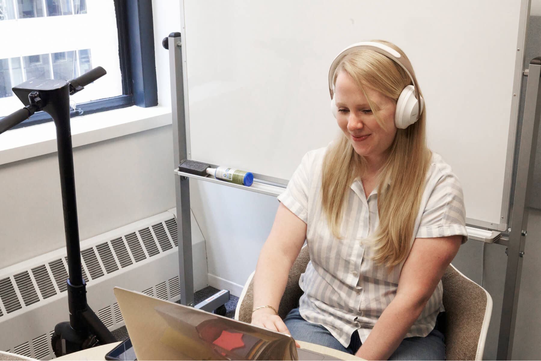 Woman sitting at a desk typing on a laptop computer wearing earphones