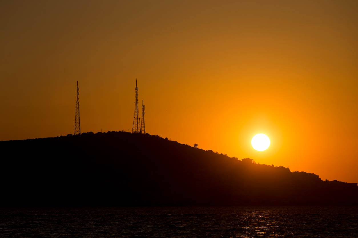 sunset behind hill with cell towers
