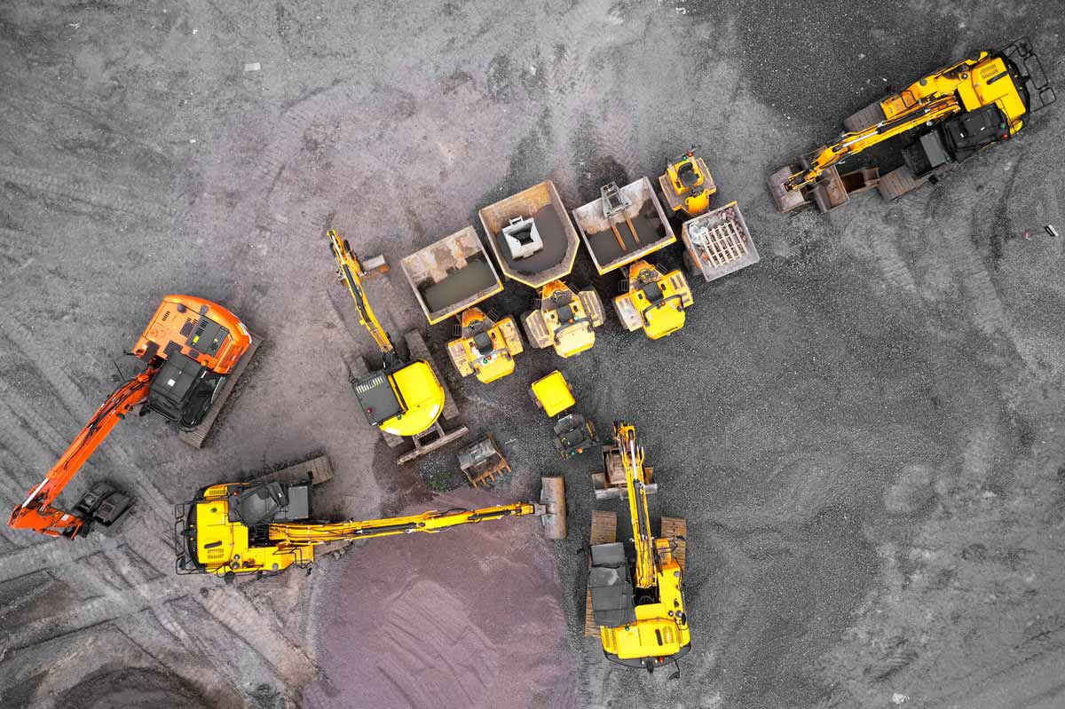 An aerial view of a construction site with yellow and orange diggers