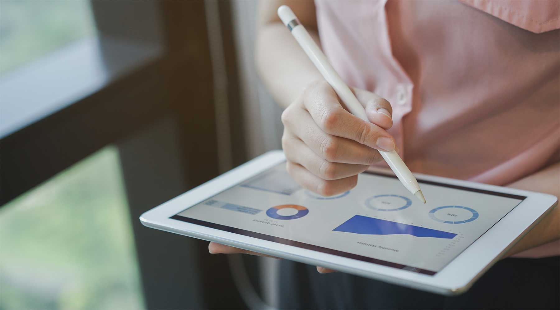 person using a tablet and stylus to monitor analytics