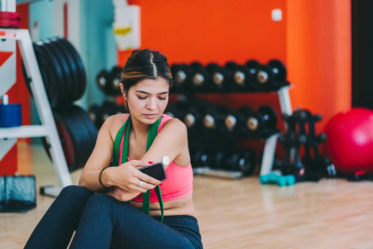 A young woman scans her glucose meter with a smart phone while sitting on the floor in a gym