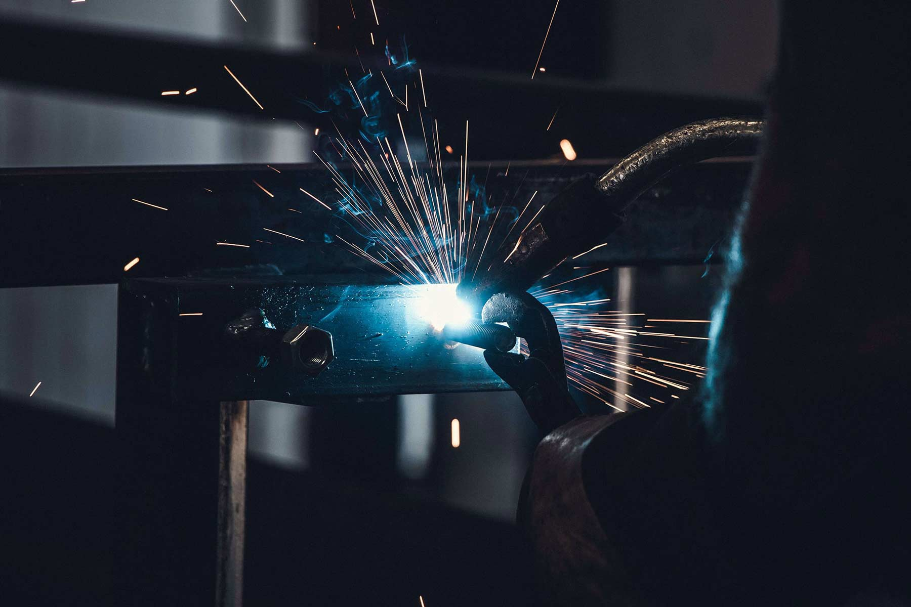male metal worker welding metal in manufacturing