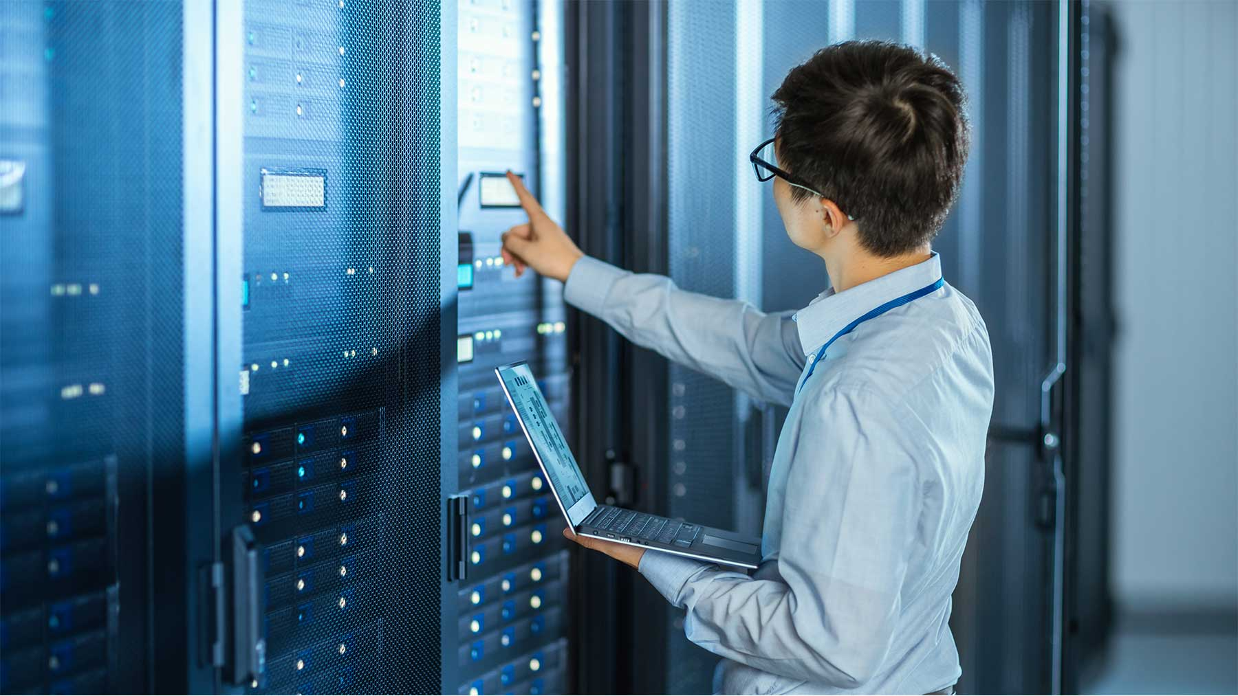 man in a server room monitoring server data