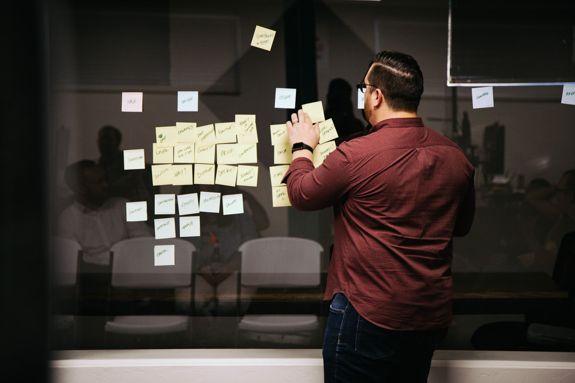 man placing post it notes on window