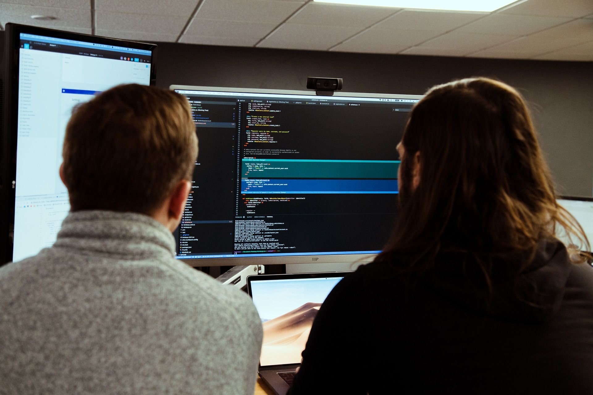 two software developers viewing code on computer screen
