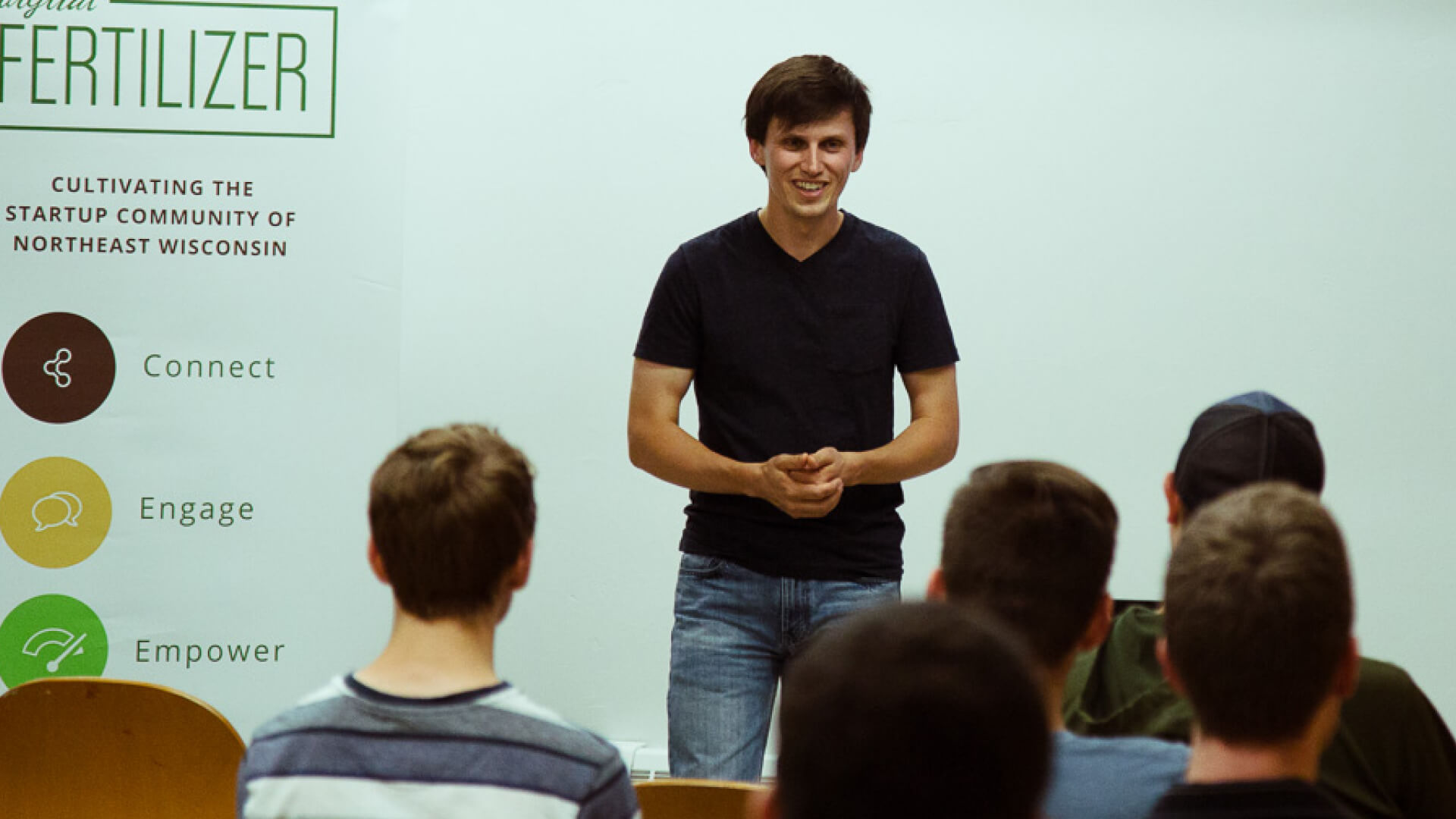 young man presenting in front of small audience