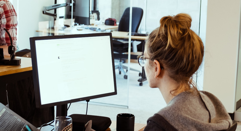 woman sitting at desk in office using computer