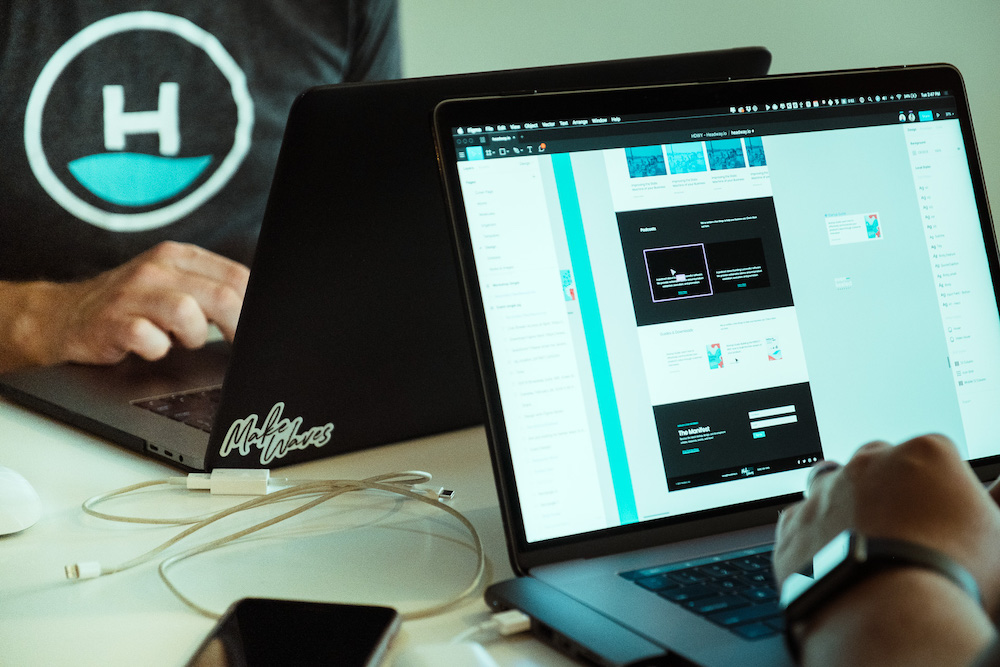 two people on macbook pros using figma app