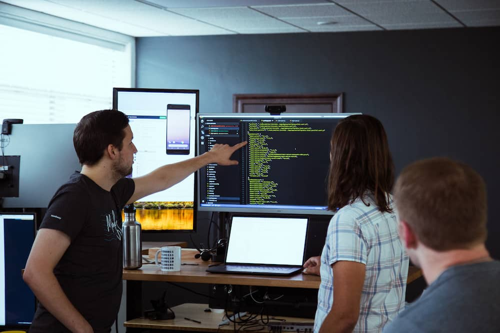 developer pointing to code on computer screen