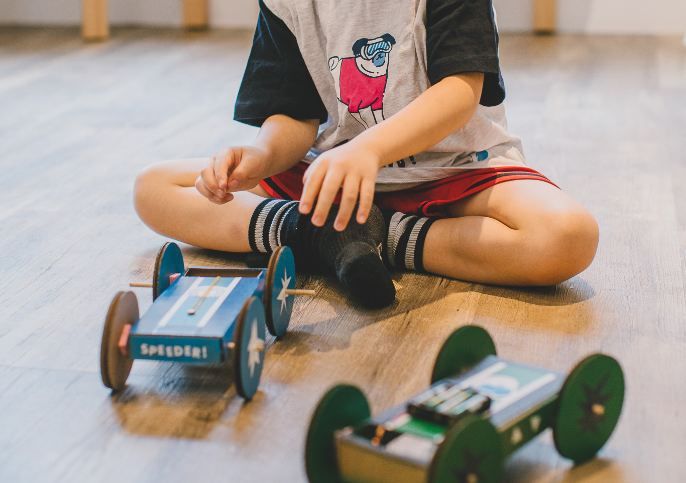 A kid plays with cardboard automated cars
