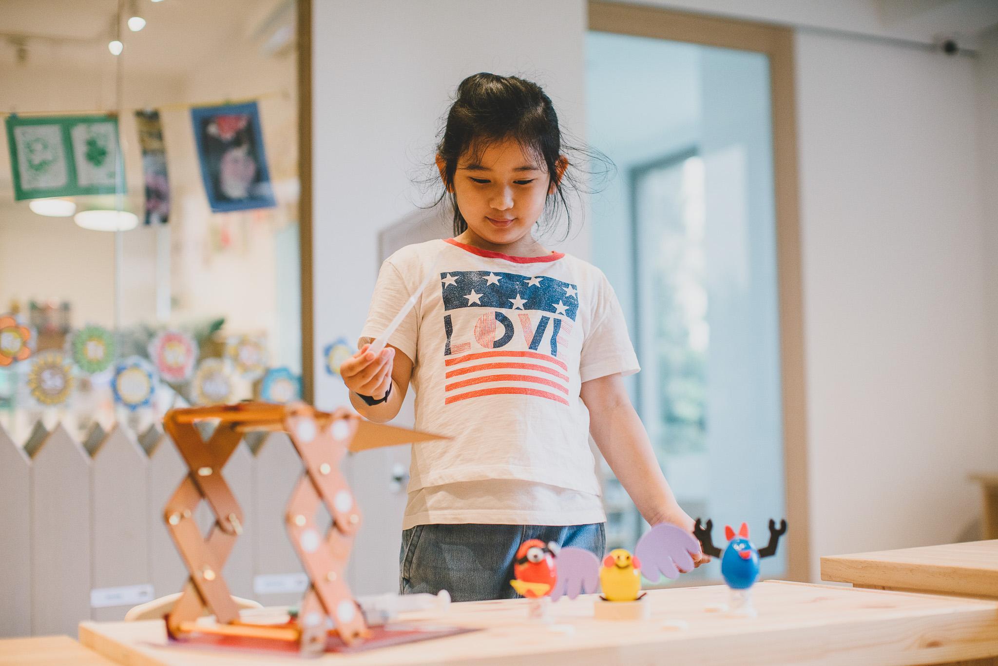 A child plays with a handmade cardboard hydraulic lift