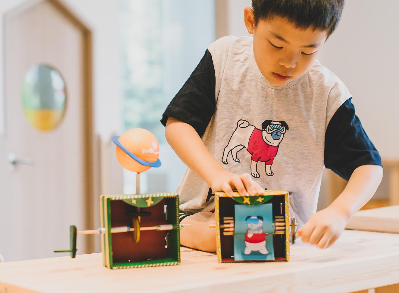 A kid is playing with a handmade thaumatrope machine animating a cartoon pug.