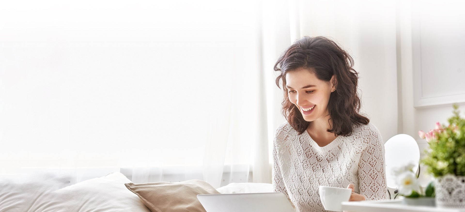 Woman smiling at the Griddy savings on her laptop