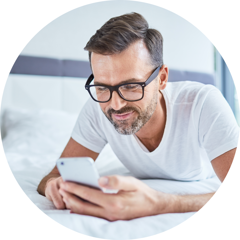 Man looking at phone on the bed