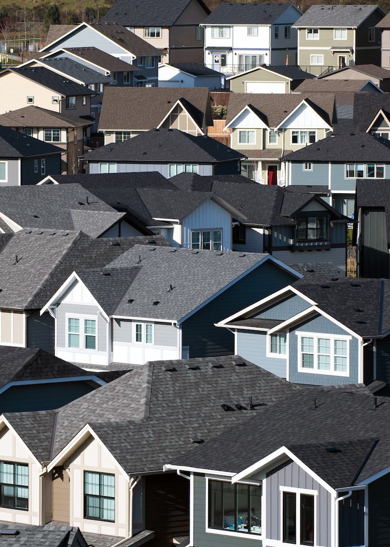 Overhead view of blue and white houses with black rooftops in Colwood, British Columbia.