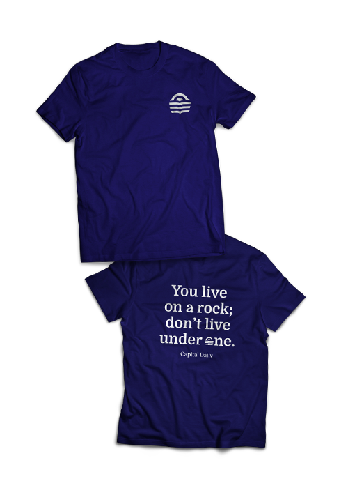"""Example of a dark purple-blue shirt, the front has the Capital Daily logo on the right chest front and the back has a slogan, """"You like on a rock; don't live under one."""""""