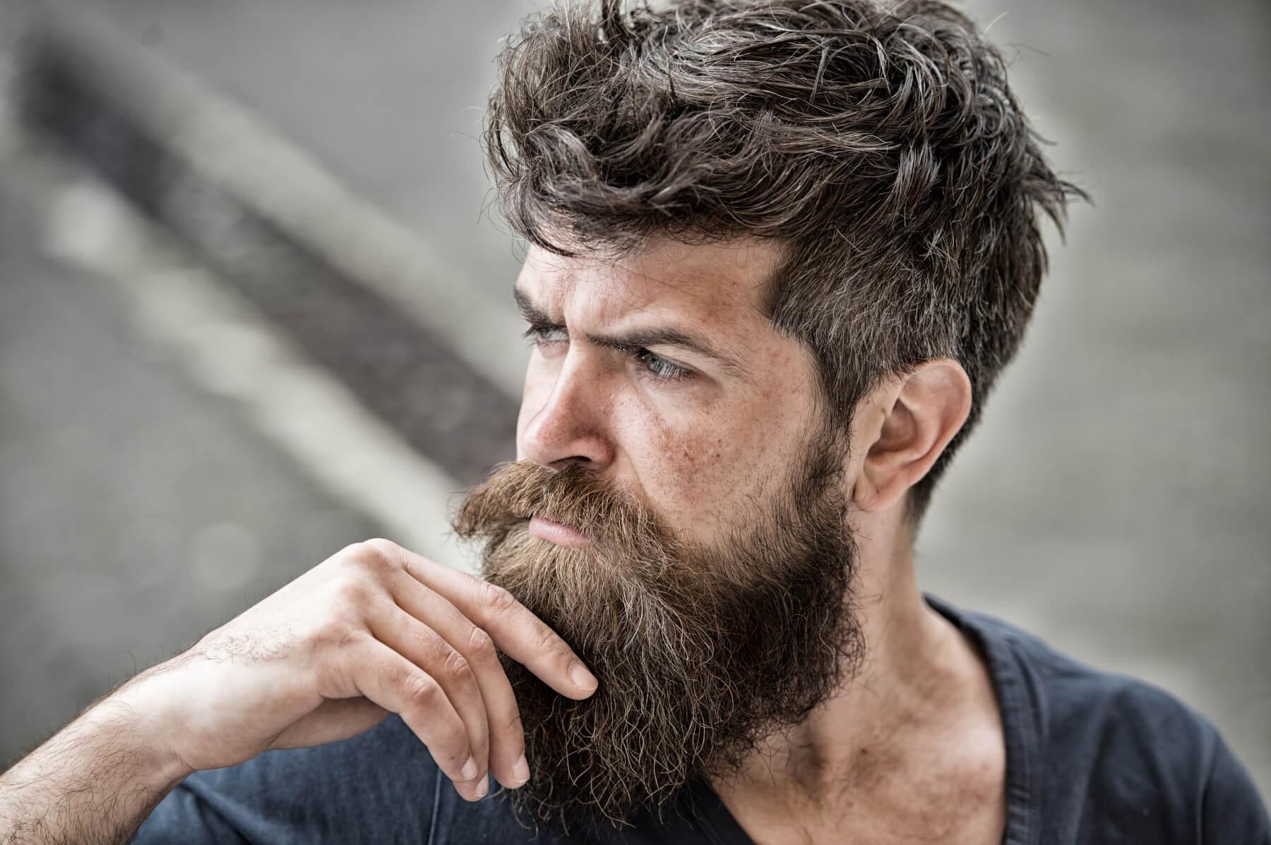 A man stroking his beard.