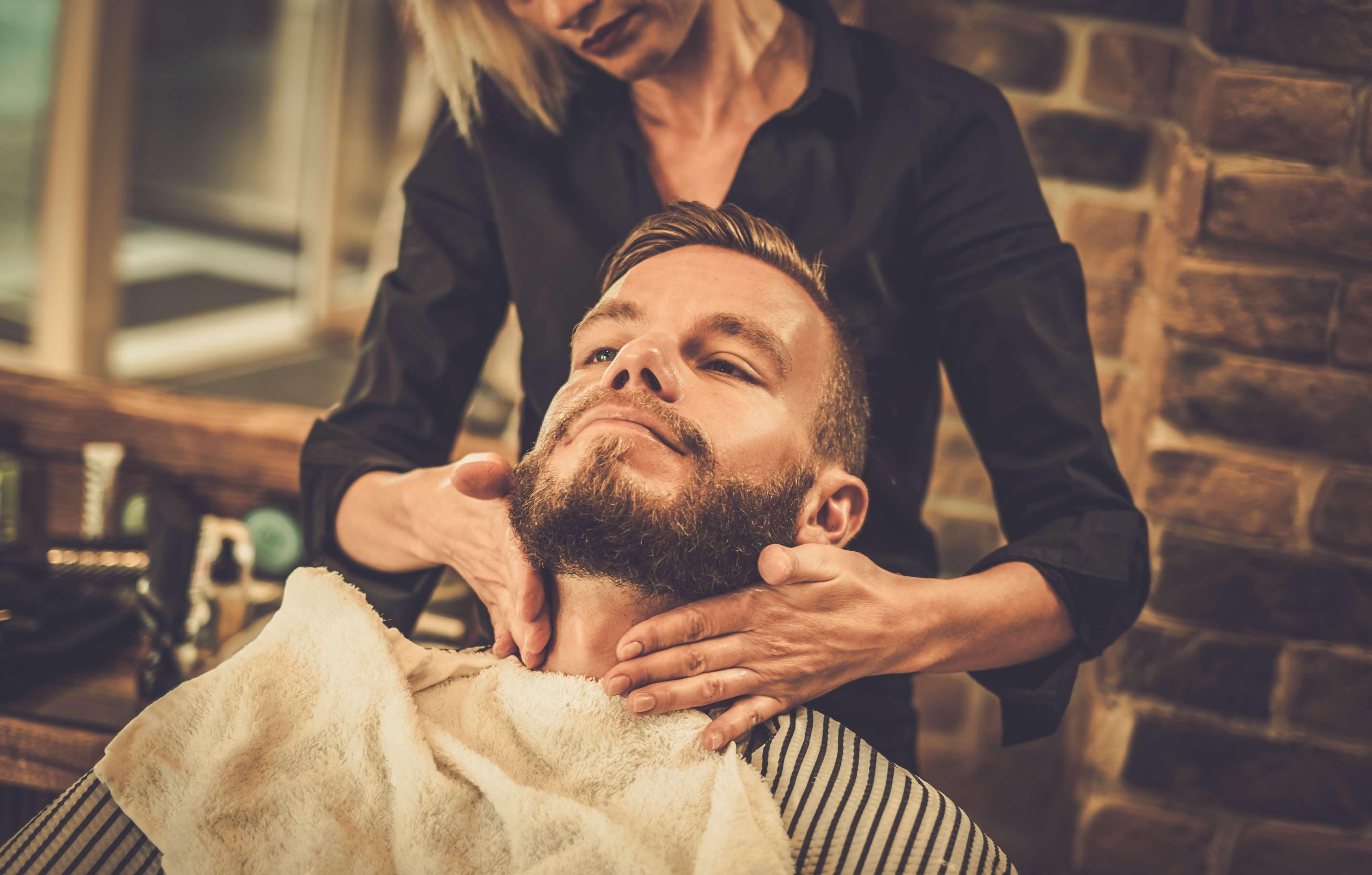 A man getting his beard groomedby a woman.